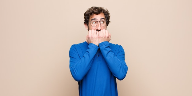 Giovane uomo bello che sembra preoccupato, ansioso, stressato e impaurito, mordendosi le unghie e cercando di copiare lo spazio laterale sulla parete piana