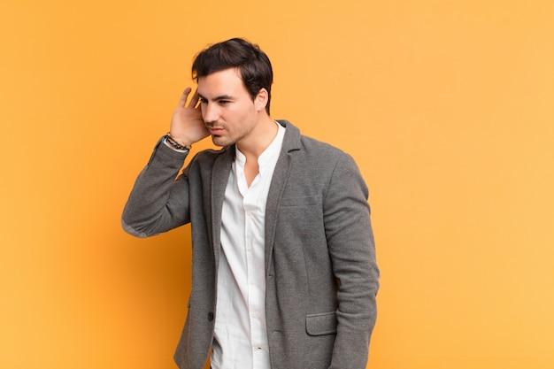 Giovane uomo bello che sembra serio e curioso, ascolta, cerca di ascoltare una conversazione o pettegolezzo segreto, origliare