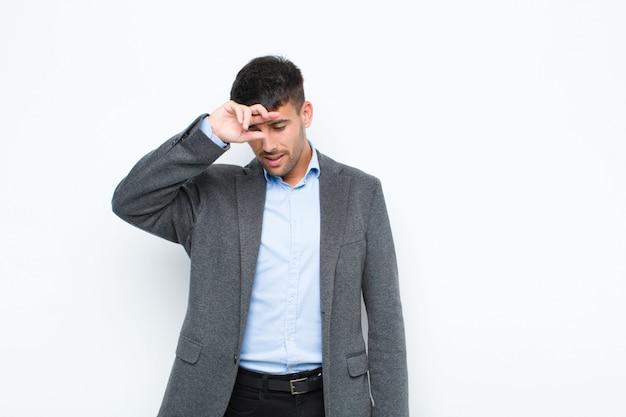 Giovane uomo bello che sembra stressato, stanco e frustrato, asciugando il sudore dalla fronte, sentendosi senza speranza ed esausto sul muro bianco