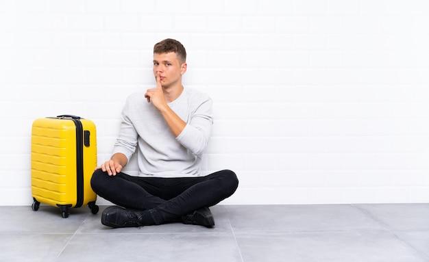 Giovane uomo bello che si siede sul pavimento con una valigia che fa gesto di silenzio