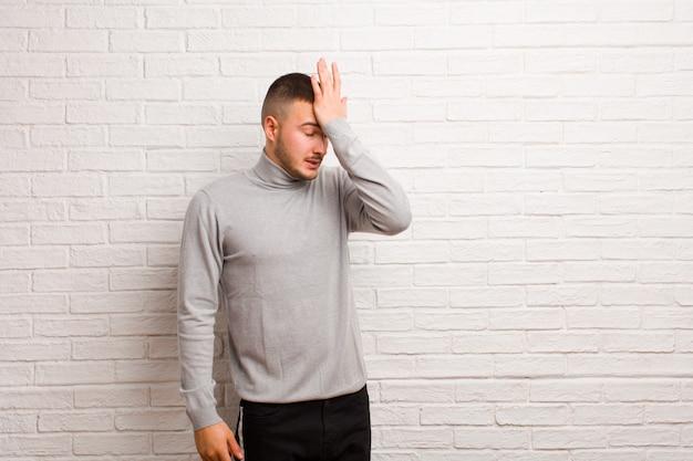 Giovane uomo bello che solleva il palmo alla fronte pensando oops, dopo aver fatto uno stupido errore o aver ricordato, sentendosi stupido