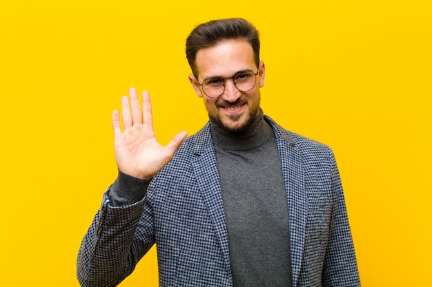 Giovane uomo bello che sorride allegramente e allegramente, agitando la mano, dandovi il benvenuto e salutandovi, o salutandovi contro la parete arancione