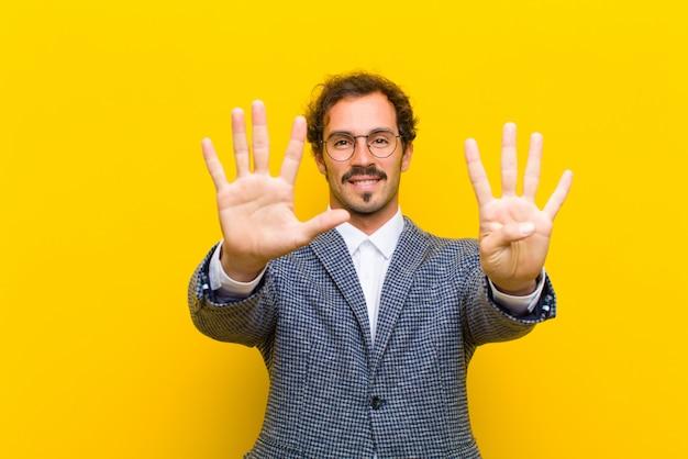 Giovane uomo bello che sorride e che sembra amichevole, mostrando numero diciannovesimo con la mano in avanti, conto alla rovescia della parete arancione