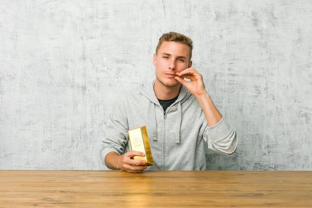 Giovane uomo bello che tiene un lingotto d'oro su un tavolo con le dita sulle labbra mantenendo un segreto.
