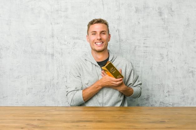 Giovane uomo bello che tiene un lingotto dell'oro su una tavola che ride tenendo le mani sul cuore, concetto di felicità.