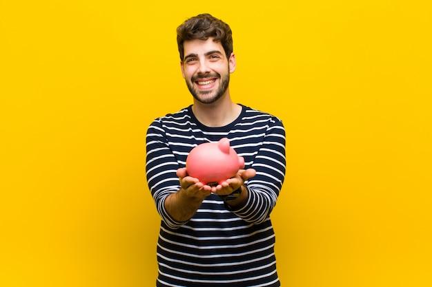 Giovane uomo bello che tiene un porcellino salvadanaio sull'arancia