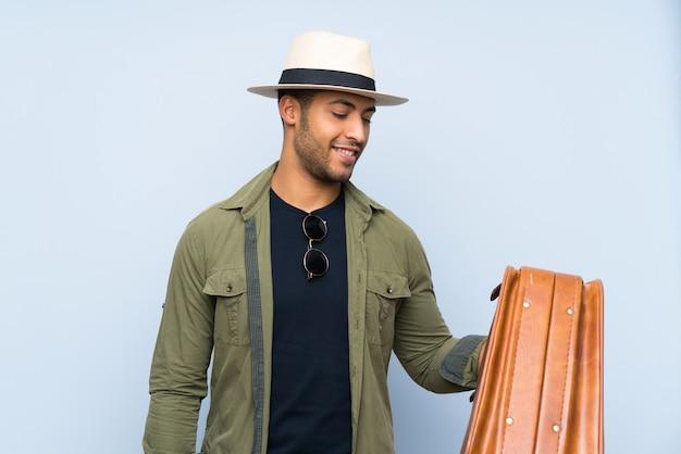 Giovane uomo bello che tiene una cartella d'annata sopra la parete blu isolata con l'espressione felice
