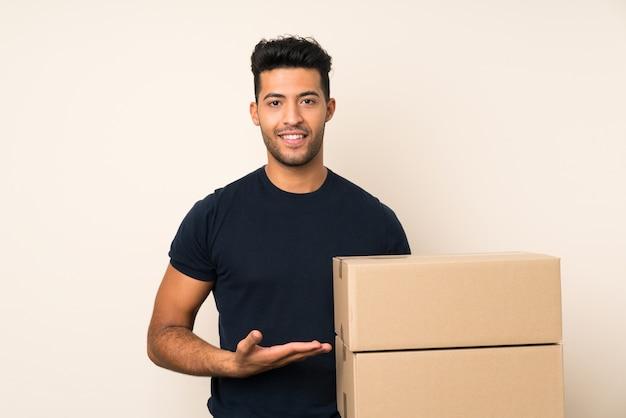 Giovane uomo bello che tiene una scatola per spostarla in un altro sito