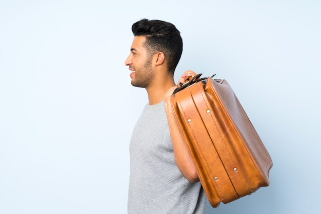 Giovane uomo bello che tiene una valigetta vintage