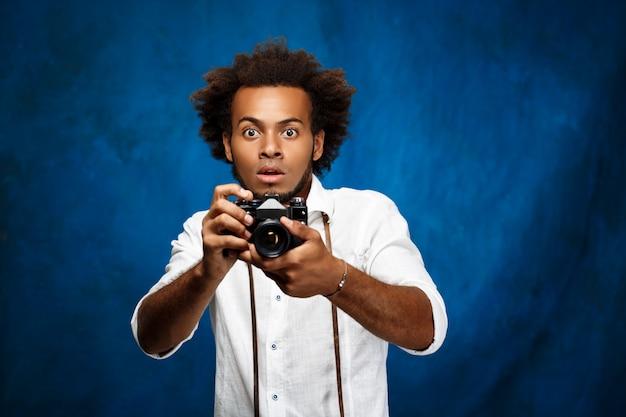 Giovane uomo bello che tiene vecchia macchina fotografica sopra la superficie del blu