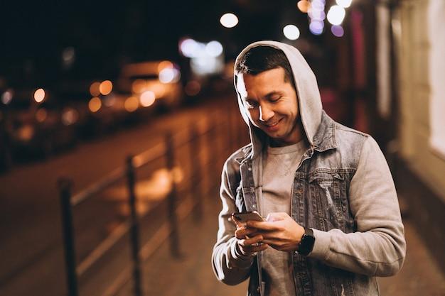 Giovane uomo bello che utilizza telefono alla notte nella via