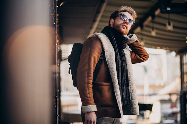 Giovane uomo bello con abiti invernali a piedi sulla strada