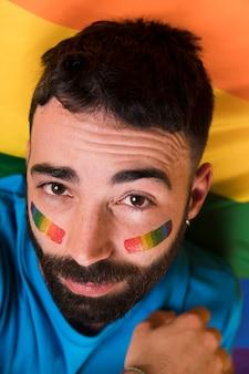 Giovane uomo bello con bandiera arcobaleno lgbt sul viso