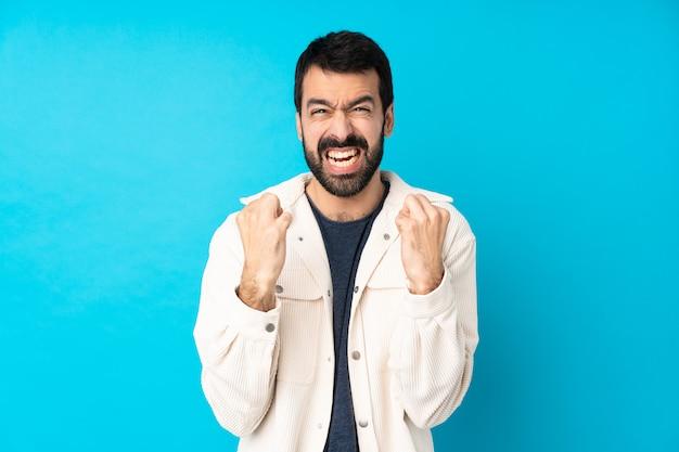 Giovane uomo bello con giacca di velluto bianco su muro blu isolato frustrato da una brutta situazione