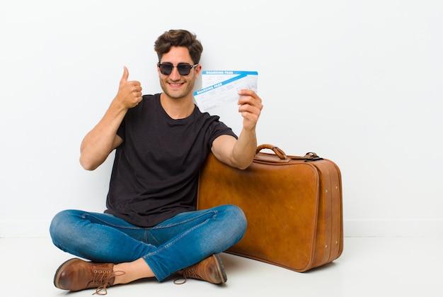 Giovane uomo bello con i biglietti di una carta d'imbarco che si siedono sul pavimento in una stanza bianca