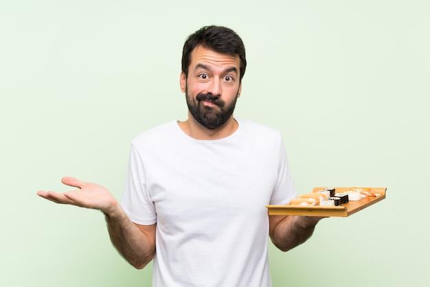 Giovane uomo bello con i sushi sopra la parete verde isolata infelice per non capire qualcosa
