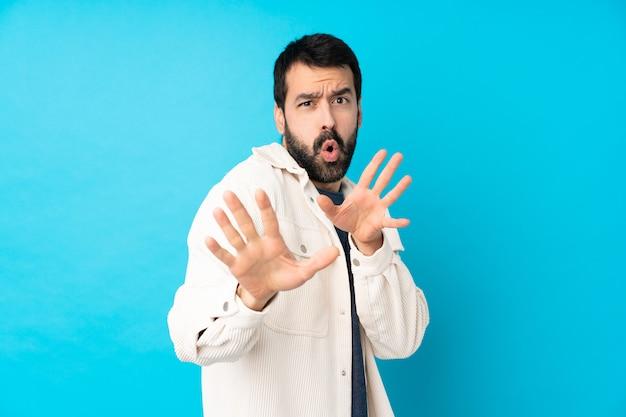Giovane uomo bello con il rivestimento bianco del velluto a coste sopra la parete blu isolata che allunga nervosamente le mani alla parte anteriore