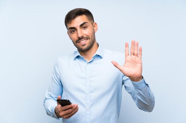 Giovane uomo bello con il suo cellulare che saluta con la mano con l'espressione felice