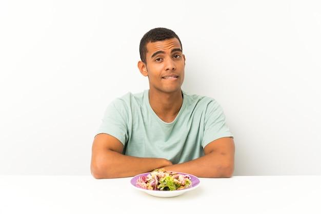 Giovane uomo bello con insalata in una tabella che ha dubbi e con espressione del viso confuso
