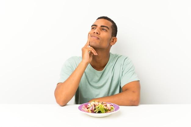 Giovane uomo bello con insalata in una tabella che pensa un'idea