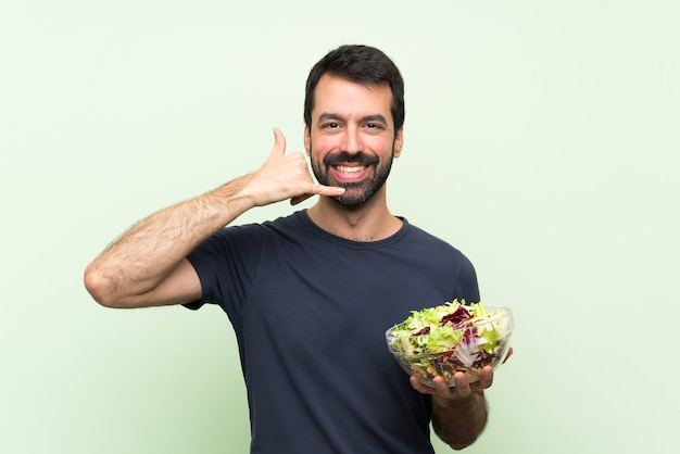 Giovane uomo bello con insalata sopra la parete verde isolata che fa gesto del telefono. richiamami segno