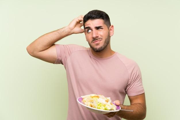 Giovane uomo bello con insalata sopra la parete verde isolata che ha dubbi e con l'espressione confusa del fronte