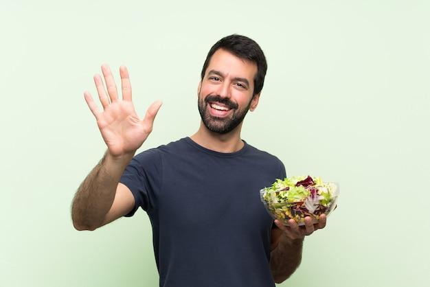 Giovane uomo bello con insalata sopra la parete verde isolata che saluta con la mano con l'espressione felice