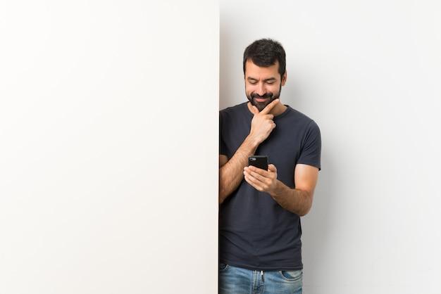 Giovane uomo bello con la barba che pensa e che invia un messaggio
