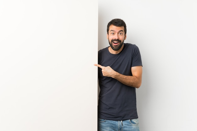 Giovane uomo bello con la barba che tiene sorpreso e indicando un grande cartello vuoto