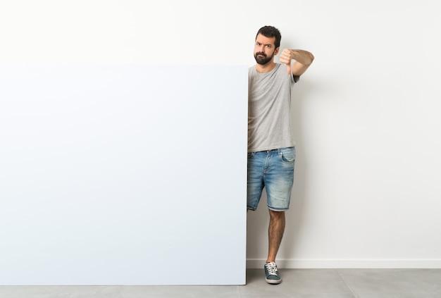 Giovane uomo bello con la barba che tiene un grande cartello vuoto blu che mostra pollice giù con l'espressione negativa