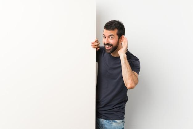 Giovane uomo bello con la barba che tiene un grande cartello vuoto che ascolta qualcosa mettendo la mano sull'orecchio
