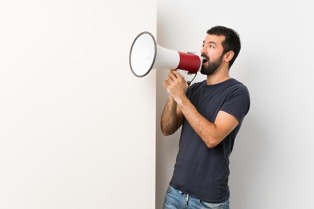Giovane uomo bello con la barba che tiene un grande cartello vuoto che grida tramite un megafono