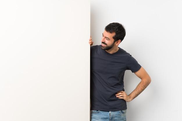 Giovane uomo bello con la barba che tiene un grande cartello vuoto che guarda al lato