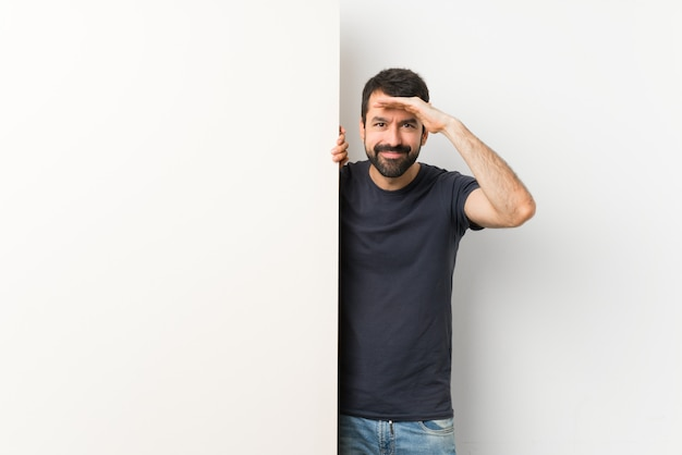 Giovane uomo bello con la barba che tiene un grande cartello vuoto che guarda lontano con la mano per guardare qualcosa