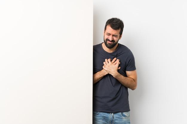 Giovane uomo bello con la barba che tiene un grande cartello vuoto che ha un dolore nel cuore