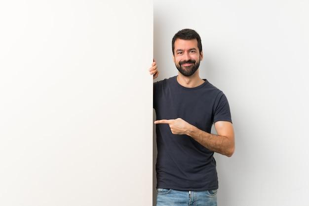 Giovane uomo bello con la barba che tiene un grande cartello vuoto che punta il dito verso il lato