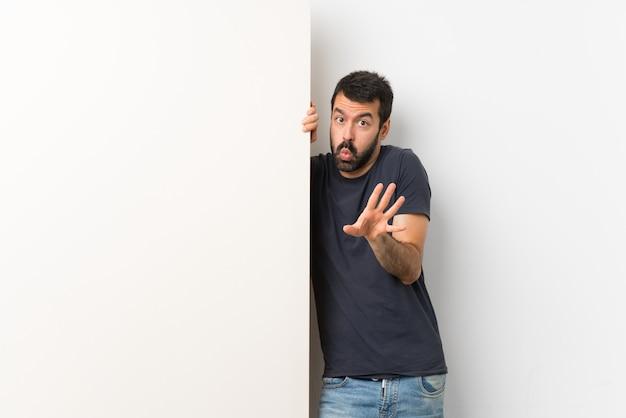 Giovane uomo bello con la barba che tiene un grande cartello vuoto nervoso allungando le mani in avanti