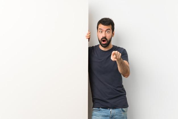 Giovane uomo bello con la barba che tiene un grande cartello vuoto sorpreso e che indica la parte anteriore
