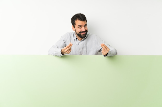 Giovane uomo bello con la barba che tiene un grande cartello vuoto verde che fa gesto di soldi