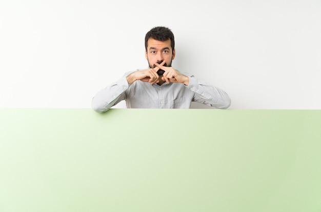 Giovane uomo bello con la barba che tiene un grande cartello vuoto verde che mostra un segno di silenzio gesto