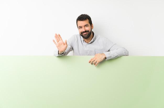 Giovane uomo bello con la barba che tiene un grande cartello vuoto verde che saluta con la mano con l'espressione felice