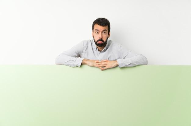 Giovane uomo bello con la barba che tiene un grande cartello vuoto verde con espressione triste e depressa