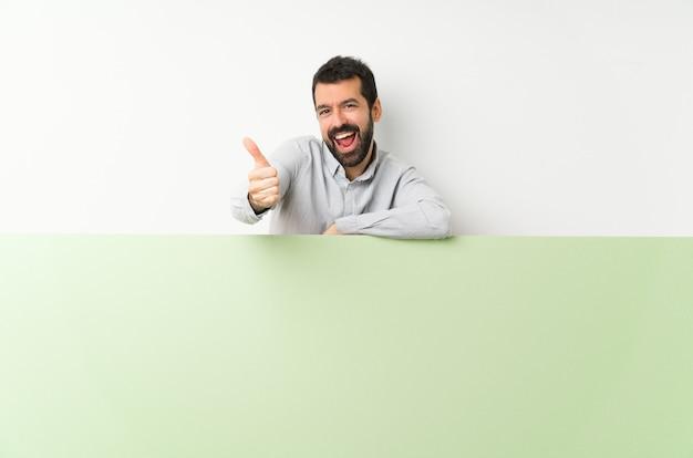 Giovane uomo bello con la barba che tiene un grande cartello vuoto verde con i pollici in su perché è successo qualcosa di buono