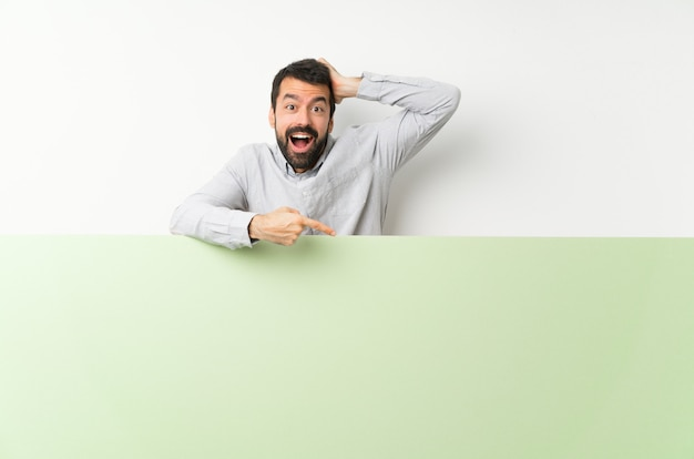 Giovane uomo bello con la barba che tiene un grande cartello vuoto verde