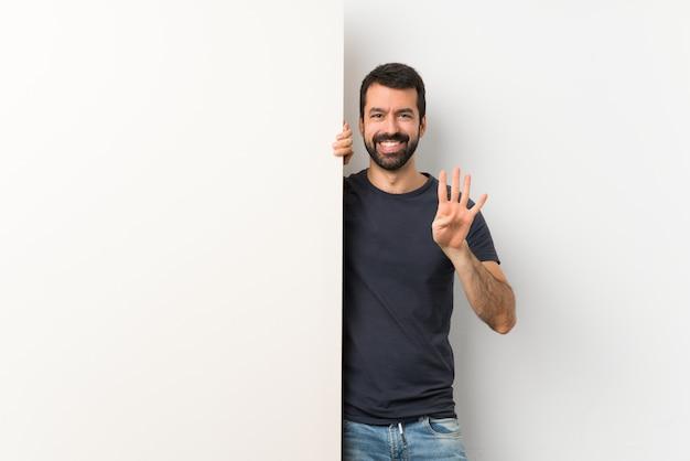 Giovane uomo bello con la barba che tiene un grande cartello vuoto