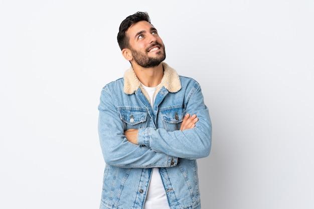 Giovane uomo bello con la barba isolata sul cercare bianco mentre sorridendo