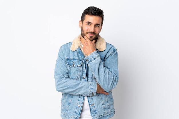 Giovane uomo bello con la barba isolata sul pensiero bianco della parete