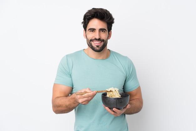 Giovane uomo bello con la barba sopra la parete bianca isolata che tiene una ciotola di noodles con le bacchette