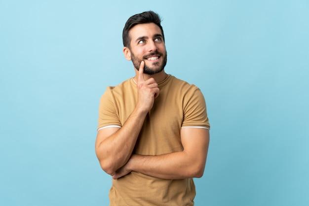 Giovane uomo bello con la barba sopra la parete isolata che pensa un'idea mentre osservando in su