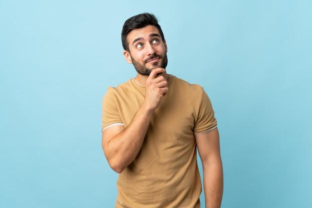 Giovane uomo bello con la barba sopra la parete isolata e cercare